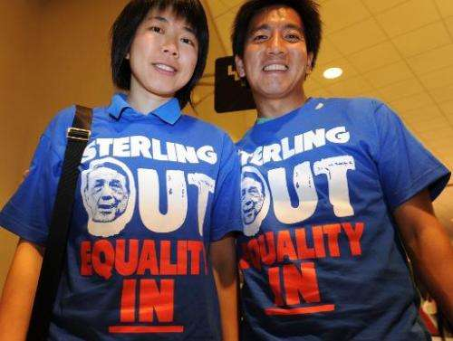 Clippers fans Kitty Siu (L) and Alvy Chen wear tee shirts calling for Donald Sterling to sell the Los Angeles Clippers on April