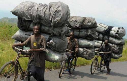 Congolese charcoal dealers push their bicycles up the hill as they transport their produce to the market in Sake, North Kivu, on