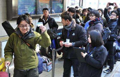 Customers receive numbered tickets outside the Sony building in Tokyo's Ginza shopping district on February 21, 2014 to purchase