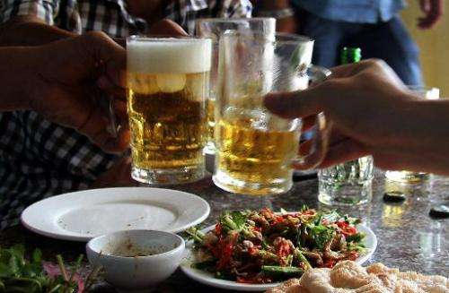 Diners enjoy a dish of cat meat while drinking beer at a restaurant in Hanoi on June 19, 2014