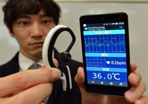 "Engineer from Japanese machinery maker NS West shows the ""Earclip-type Wearable PC"" equipped with sensors such as a pu"
