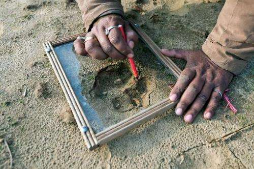 Forest guard Deepak Shukla draws pugmarks on a glass during a tiger hunt in the forest near the village of Barahpur village in B