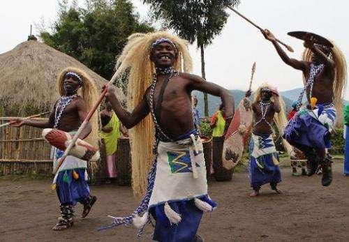Former gorilla poachers perform a dance for tourists on September 3, 2014 at Kinigi