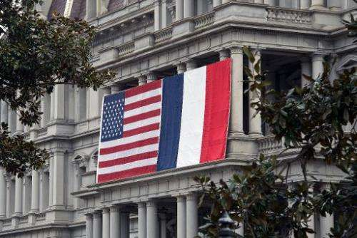 French and US flags hang on the Eisenhower Executive Office Building of the White House, in Washington, DC, on February 7, 2014,