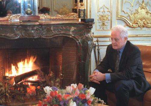 French former Prime Minister Lionel Jospin warms himself next to a fire in his Matignon office in Paris in 1998