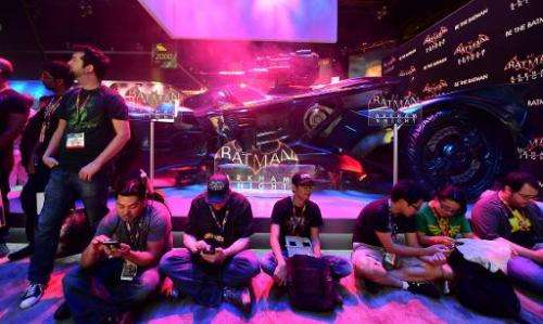 """Gaming fans take a break beside the Batman """"Arkham Knight"""" display at the annual E3 video game extravaganza in Los Ang"""