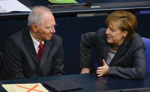 German Finance Minister Wolfgang Schaeuble (L) speaks with German Chancellor Angela Merkel before presenting his draft budget fo