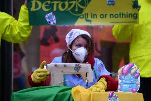 Greenpeace activists pretend they are sewing contaminated clothes with chemicals represented by little monsters, during a protes