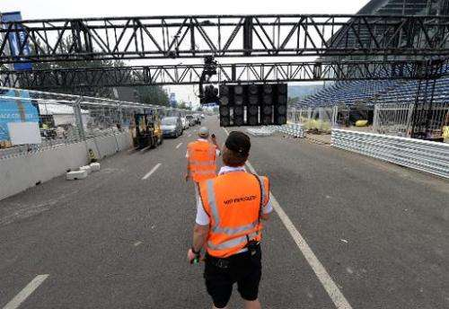 Host broadcasters set up their cameras along the race track for the Formula E debut in Beijing on September 11, 2014