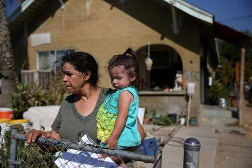 Jane Tapia (L) holds 1-year-old Melody in front of their home as they wait for a delivery of drinking water, in Porterville, Cal