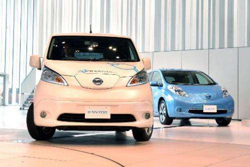 """Japanese auto maker Nissan Motor's electric vehicles """"e-NV200"""" (L) and """"Leaf"""" are pictured on June 9, 2014 a"""