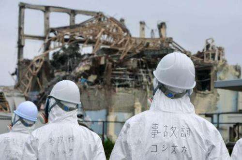 Japanese inspectors look at the damaged building housing reactor number three at the Fukushima nuclear facility at Okuma, on Jun