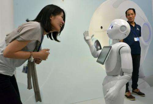 "Japanese mobile communication giant Softbank's humanoid robot ""Pepper"" (R) chatting to a woman at a high-tech gadgets"