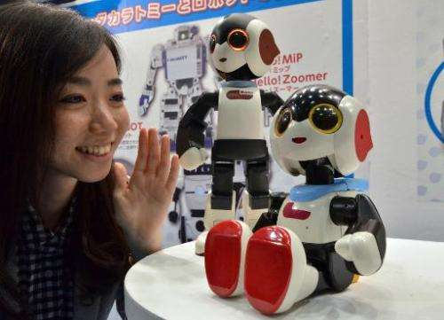 "Japan's toy maker Tomy employee enjoys a conversation with a little humanoid robot ""Robi jr."" which can speak some 1,0"