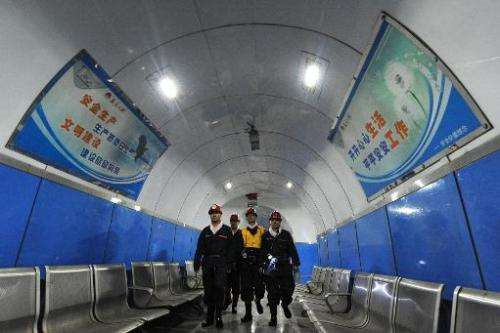 Laborers walk inside a coal mining facility in Huaibei, in northern China's Anhui province, on March 4, 2014