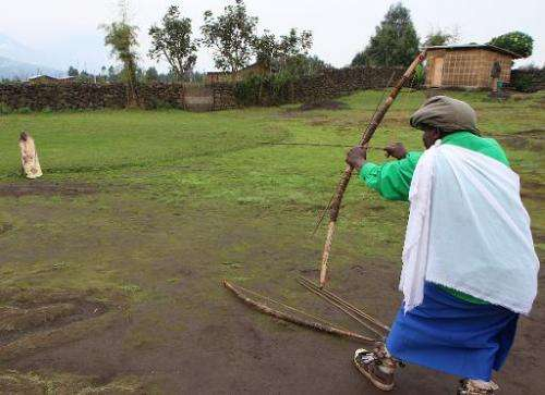 Leonidas Barora (L), a former poacher, shoots at a target using a traditional bow and arrow during a show for tourists at Kinigi