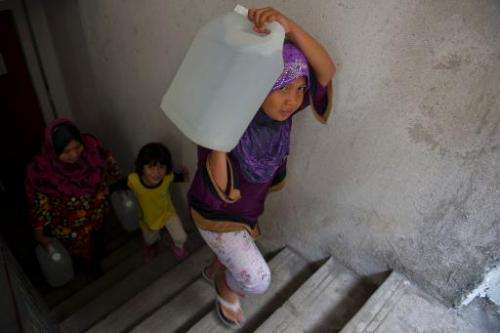Maisarah Izzati, 12, (R) a daughter of Norlizan, carries a water container in Balakong, outside Kuala Lumpur on February 25, 201