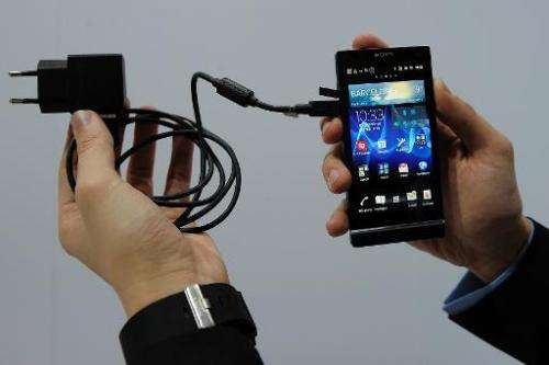 Man displays universal charger plugged in a mobile phone during a presentation at the Mobile World Congress on February 28, 2012