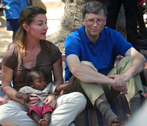 Microsoft founder and philanthopist Bill Gates (R) looks on as his wife Melinda holds a toddler during their visit to a village