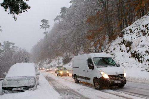 Motorists drive cars on a snow-covered road on November 21, 2013 at the Vizzavona mountain pass, near Bocognano, on the French M