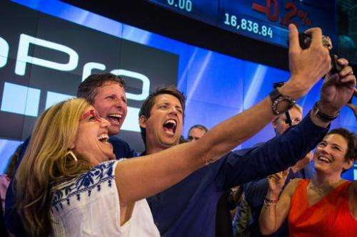 Nick Woodman (R), founder and CEO of GoPro, takes a selfie with coworkers during the company's initial public offering at the Na