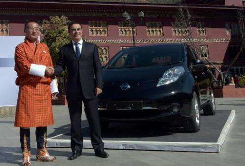 Nissan Motor CEO, Carlos Ghosn (R), and Bhutanese Prime Minister, Tshering Tobgay, unveil the Nissan Leaf electric vehicle in Th