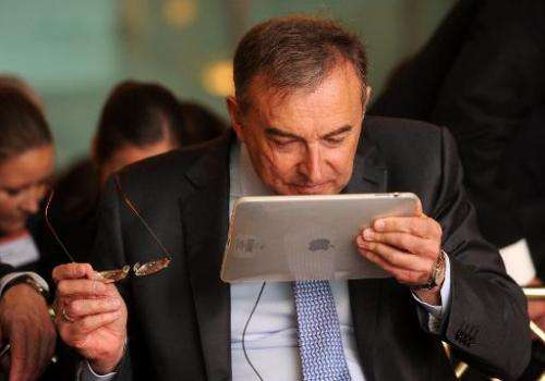 Norbert Reithofer, CEO of German car maker BMW reads on an iPad during the Handelsblatt car summit 2013 in Munich, western Germa