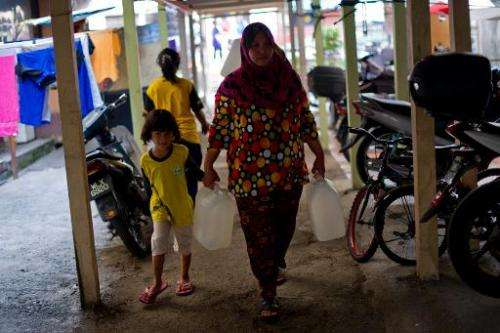 Norlizan, 40, (R), walks as she carries water containers in Balakong, outside Kuala Lumpur on February 25, 2014