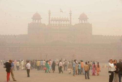 Pedestrians and visitors gather as smog envelopes The Red Fort in New Delhi on November 7, 2009
