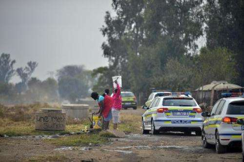 People fill buckets with water in the restive township of Gugulethu, near Cape Town, on May 6, 2014