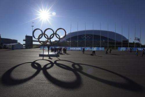People pose in front of the Olympic rings near the Bolshoy arena in the seaside cluster prior to the start of the 2014 Sochi Win