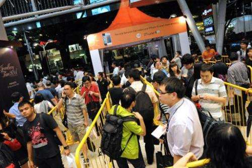 People queue outside a telecom store in Singapore on October 27, 2011 to be the first to own the new iPhone 4s at midnight