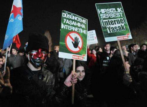 "People shout slogans as they hold placards that read ""stop censorship"" during a rally against a bill that allow Turkey"