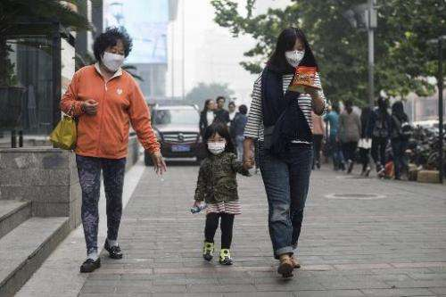 People wear face masks in Beijing amid heavy smog on October 10, 2014