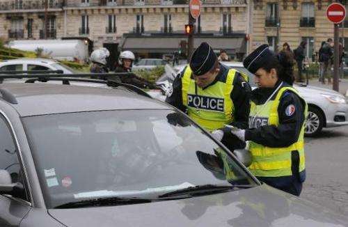 Police officers control a car in Paris, on March 17, 2014 as Paris resorted to drastic measures to curb soaring pollution levels