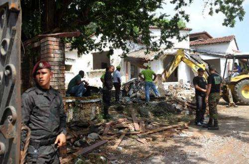 Police stand guard at the residence of Panama's former dictador Manuel Antonio Noriega, as it is demolished on January 9, 2014 f