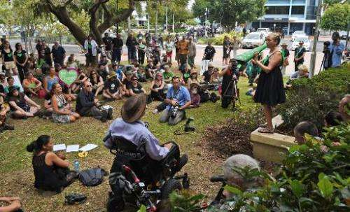 Protesters listen to a speech by an environmental activist (R) outside the G20 Finance Ministers and Central Bank Governors Meet