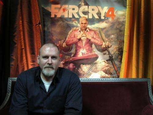 """Far Cry 4"" video game executive director Dan Hay sits in front of a poster for the Ubisoft title on October 9, 2014,"