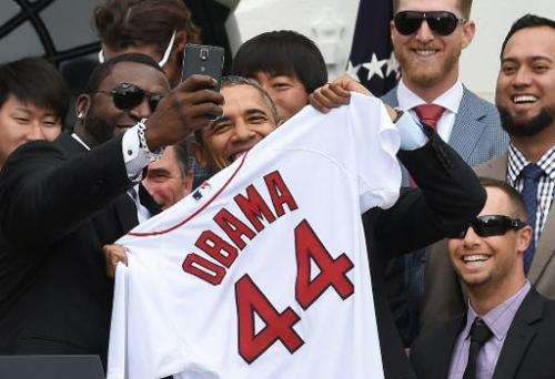 """Red Sox Designated Hitter David Ortiz (L) takes a """"selfie"""" with US President Barack Obama during a ceremony on the Sou"""