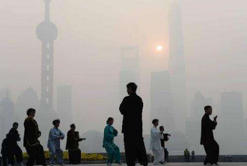 Residents exercise amid heavy smog on the Bund waterfront in Shanghai on November 12, 2014