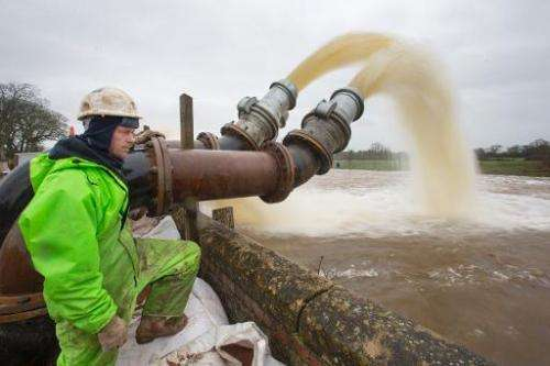 Rob Bessant checks pipes moving flood water from fields into the River Parrett at Northmoor Green in Somerset, southwest England