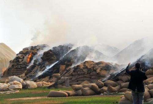Sacks of wheat burn following Syrian air strikes in the town of Ras al-Ain near the border with Turkey on November 16, 2012