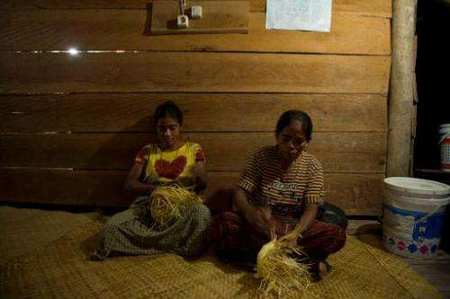 "Sumbanese women weave baskets uder a lamp powered by electricity from mini hydroelectric generators—known as ""microhydro pl"