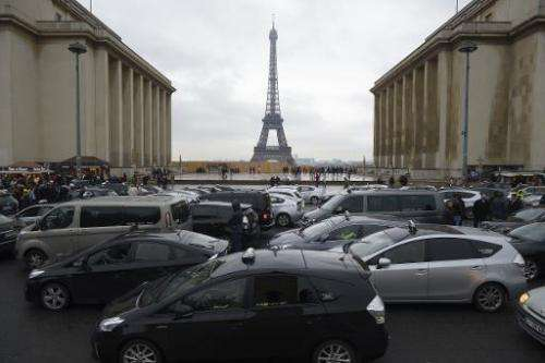 """Taxi drivers take part in a """"snail operation"""" after parking their cars on the Trocadero square in Paris, on December 1"""