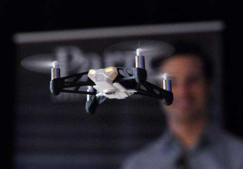 """Technology journalist Tim Stenovec controls a Parrot Minidrone """"Rolling Spider"""" during a demonstration in New York on"""