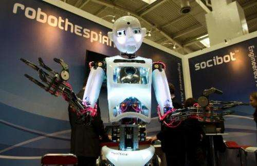 "The lifesize humanoid robot ""RoboThespian"" interacts with visitors to the Engineered Arts stand at CeBIT on March 11,"