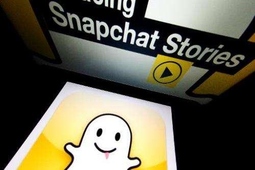 """The logo and a page of mobile app """"Snapchat"""" are displayed on tablets on January 2, 2014 in Paris"""