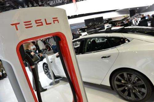 The Tesla P85+ all electric car and its charging station are displayed at the North American International Auto Show on January