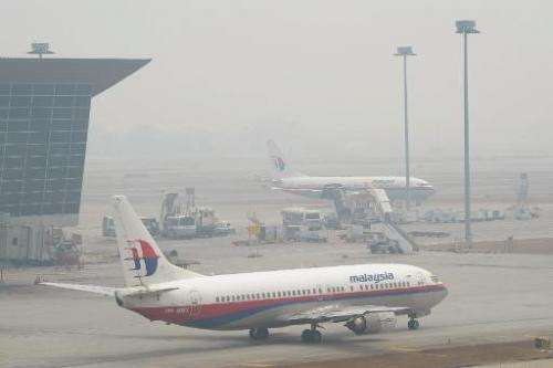 Two Malaysian Airlines planes are seen obscured by haze on the tarmac at Kuala Lumpur International Airport, in Sepang, on March