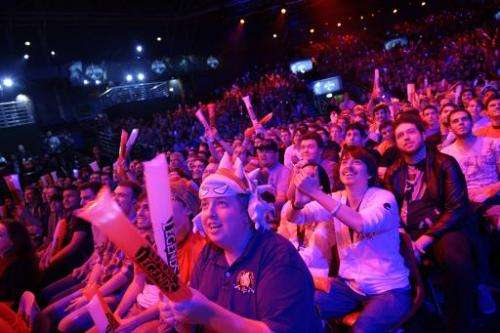 "Visitors cheer for international teams during the tournament of the computer game ""League of Legends"" on May 8, 2014 i"